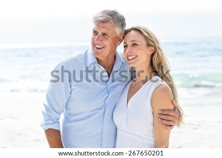Happy couple standing by the sea at the beach - stock photo