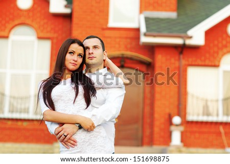Happy couple standing in front of new home - stock photo