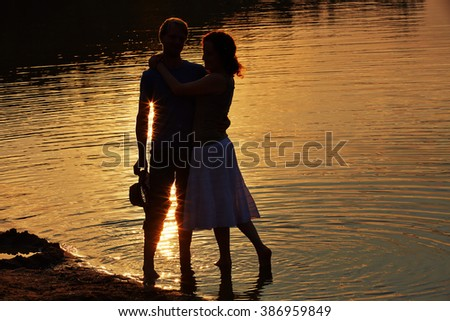 Happy couple standing in lake at sunset in summer