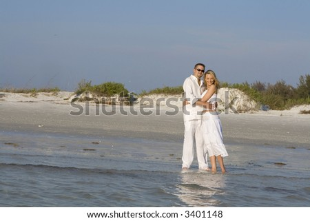 Happy couple standing on a beach, looking towards the ocean. - stock photo