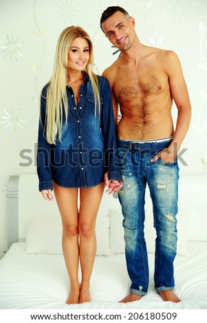 Happy couple standing on the bed at home - stock photo