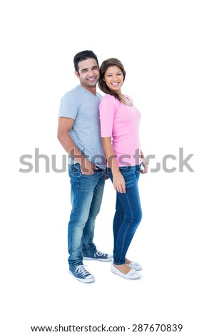 Happy couple standing together and looking at camera on white background