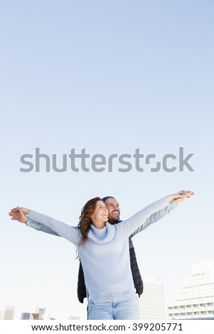 Happy couple standing with arms outstretched - stock photo