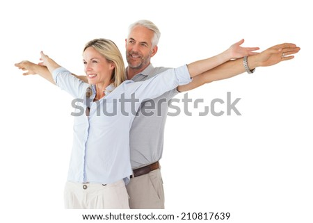 Happy couple standing with arms outstretched on white background - stock photo
