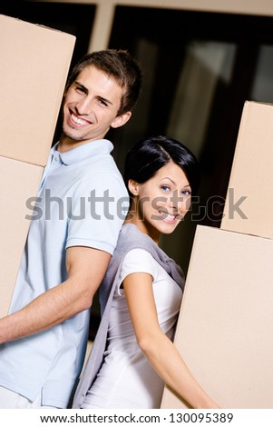 Happy couple stands back to back while carrying cardboard packages and moving to new house - stock photo