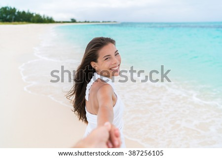Happy couple summer vacation travel - Asian woman on romantic honeymoon beach holiday holding hand of boyfriend looking at camera. Man following girlfriend walking. POV. - stock photo