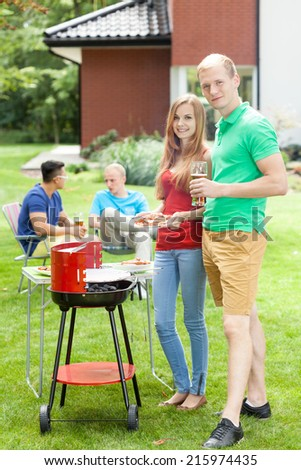 Happy couple supporting grill on a garden party - stock photo