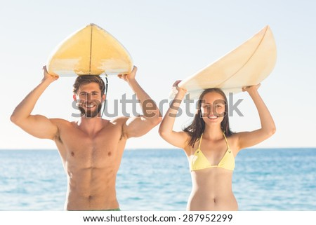 happy couple surfing at the beach - stock photo