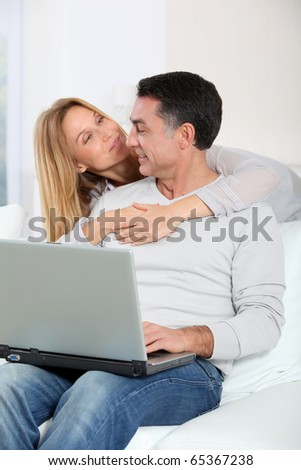 Happy couple surfing on internet at home