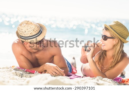 Happy couple taking a photo at the beach - stock photo