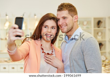 Happy couple taking a selfie photo with smartphone in a jewelry store - stock photo