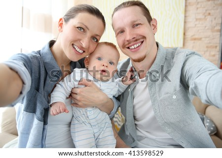 Happy couple taking a selfie with baby , close up - stock photo