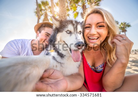 Happy couple taking a selfie with their husky - Dog holding camera and taking a funny picture with his family