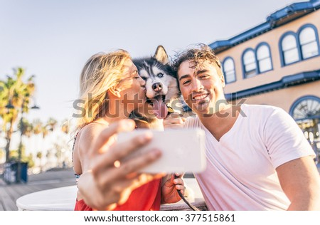 Happy couple taking a selfie with their husky - Woman holding cellphone and taking a funny picture with his family - stock photo