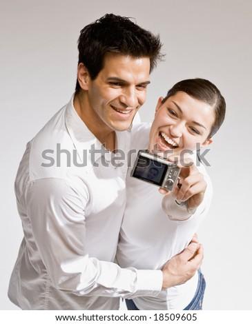 Happy couple taking self-portrait with digital camera - stock photo