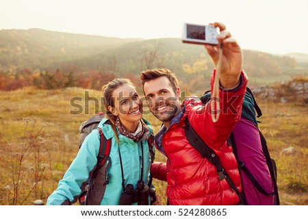 Happy couple taking selfie during autumn, fall hiking adventure