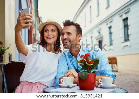 Happy couple taking selfie in outdoor cafe - stock photo