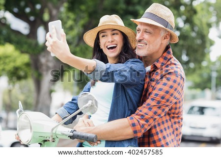 Happy couple taking selfie on moped in city - stock photo
