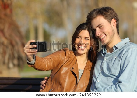 Happy couple taking selfie photos sitting in a bench in a park - stock photo