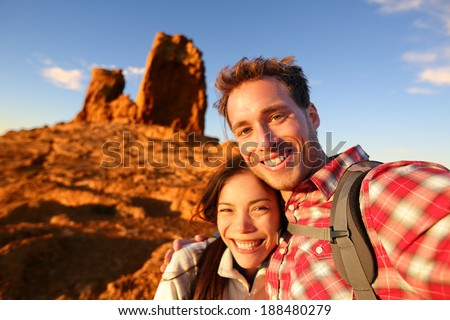 Happy couple taking selfie self-portrait photo hiking. Two friends or lovers on hike smiling at camera outdoors mountains by Roque Nublo, Gran Canaria, Canary Islands, Spain. - stock photo
