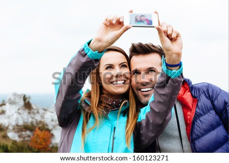 Happy couple taking snapshot of themselves - stock photo