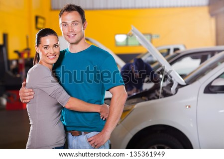 happy couple taking their car for service and waiting inside garage - stock photo