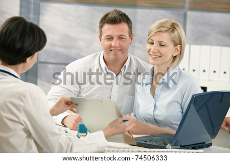 Happy couple talking to medical specialist, sitting at doctor's office smiling.? - stock photo
