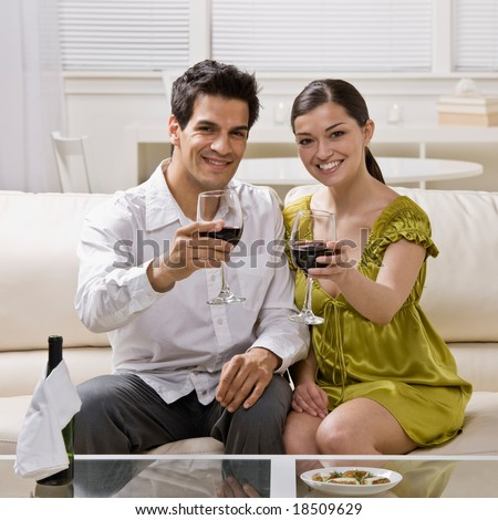Happy couple toasting and drinking red wine celebrating anniversary - stock photo