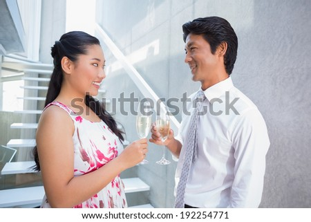 Happy couple toasting with champagne on the stairs - stock photo