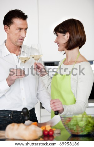 Happy Couple Toasting With Glass Of Wine while preparing dinner - stock photo