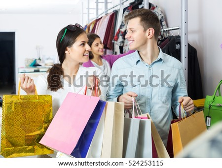 Happy couple together carrying bags with purchases and smiling in boutique