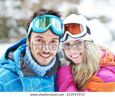Happy couple together on a ski trip in winter - stock photo