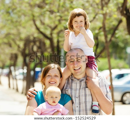 Happy couple together with children in summer street