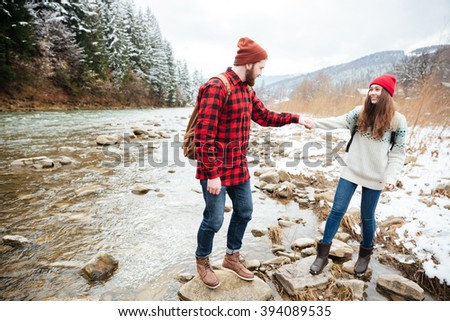Happy couple traveling on the river in forest