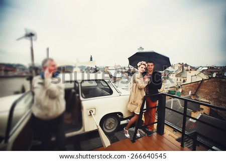 happy couple under an umbrella on a background of the old city - stock photo
