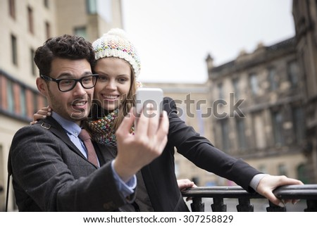Happy couple using a Smart Phone to take a 'Selie' self portrait. Outdoors in the city. - stock photo