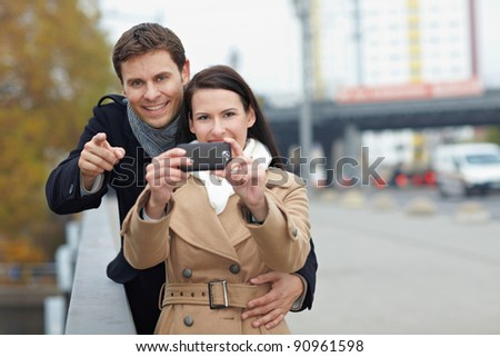Happy couple using camera in mobile phone in a city - stock photo