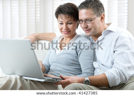 happy couple using laptop at home - stock photo