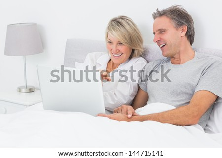 Happy couple using laptop in bed together at home