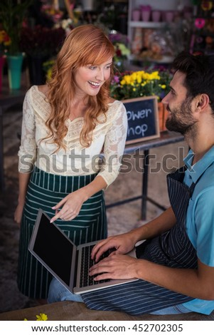 Happy couple using laptop in the flower shop - stock photo