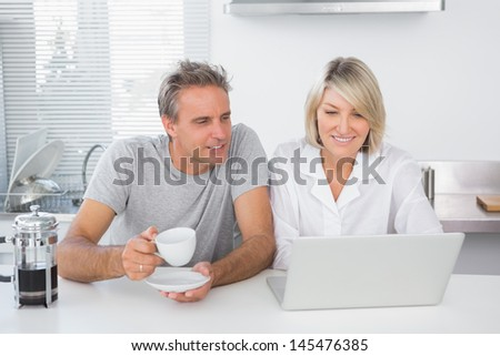 Happy couple using laptop in the morning sitting at kitchen counter - stock photo