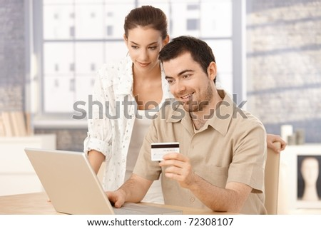 Happy couple using laptop, shopping online at home, using credit card.? - stock photo
