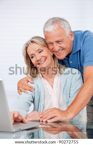 Happy couple using laptop together at home - stock photo