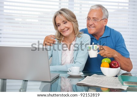 Happy couple using laptop while having breakfast - stock photo