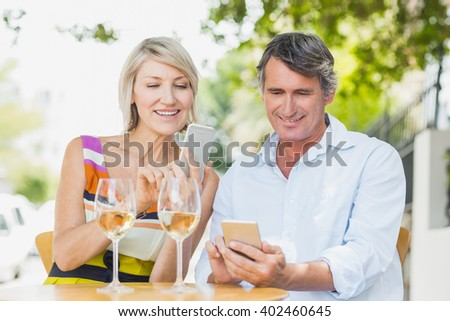 Happy couple using mobile phone at cafe