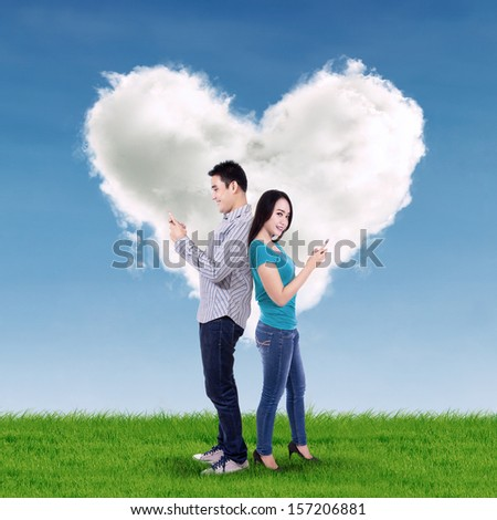 Happy couple using mobile phone over heart shaped cloud - stock photo
