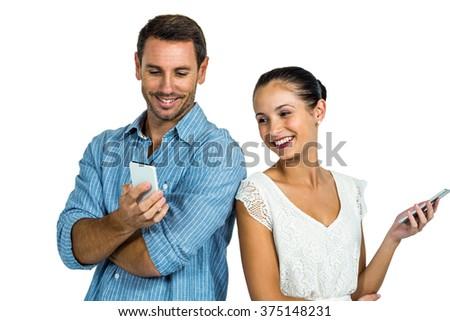 Happy couple using smartphones on white screen - stock photo