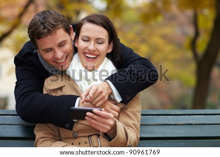 Happy couple using Social Media with a smartphone - stock photo