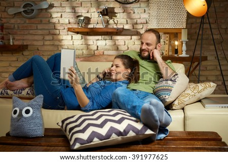 Happy couple using tablet computer at home, relaxing on sofa.