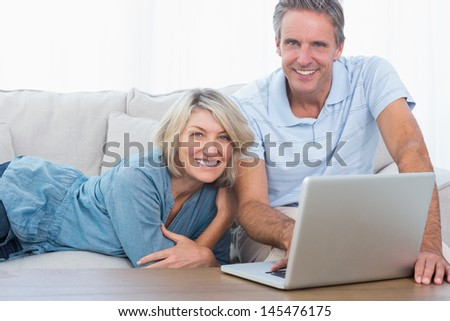 Happy couple using their laptop looking at camera at home on the couch